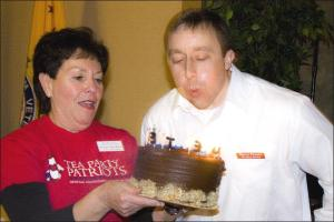 """Elaine Meckler presents Barry Pruett with a birthday cake while we all sing Happy Birthday! (Photo credit: http://www.mcguiresplace.net/Events-Nevada%20County%20Tea%20Party%20Party%20Jan%202010/"